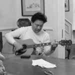 Delta Bohemian Gene Joe playing Magical Madge's Epiphone shortly after he restrung it. Note the Marshall Bouldin pencil sketch behind him. Photo by The DB