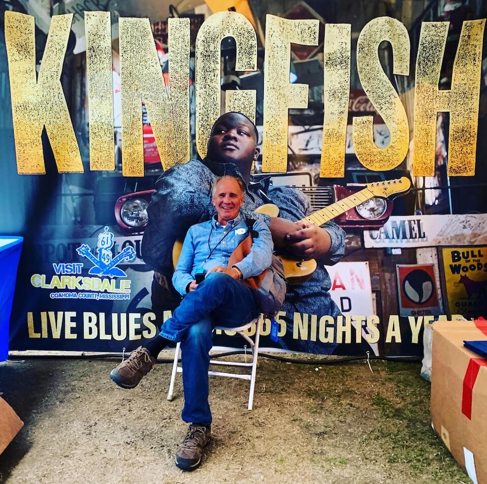 Clarksdale Tourism Executive Director Bubba O'Keefe in front of the cover of Kingfish